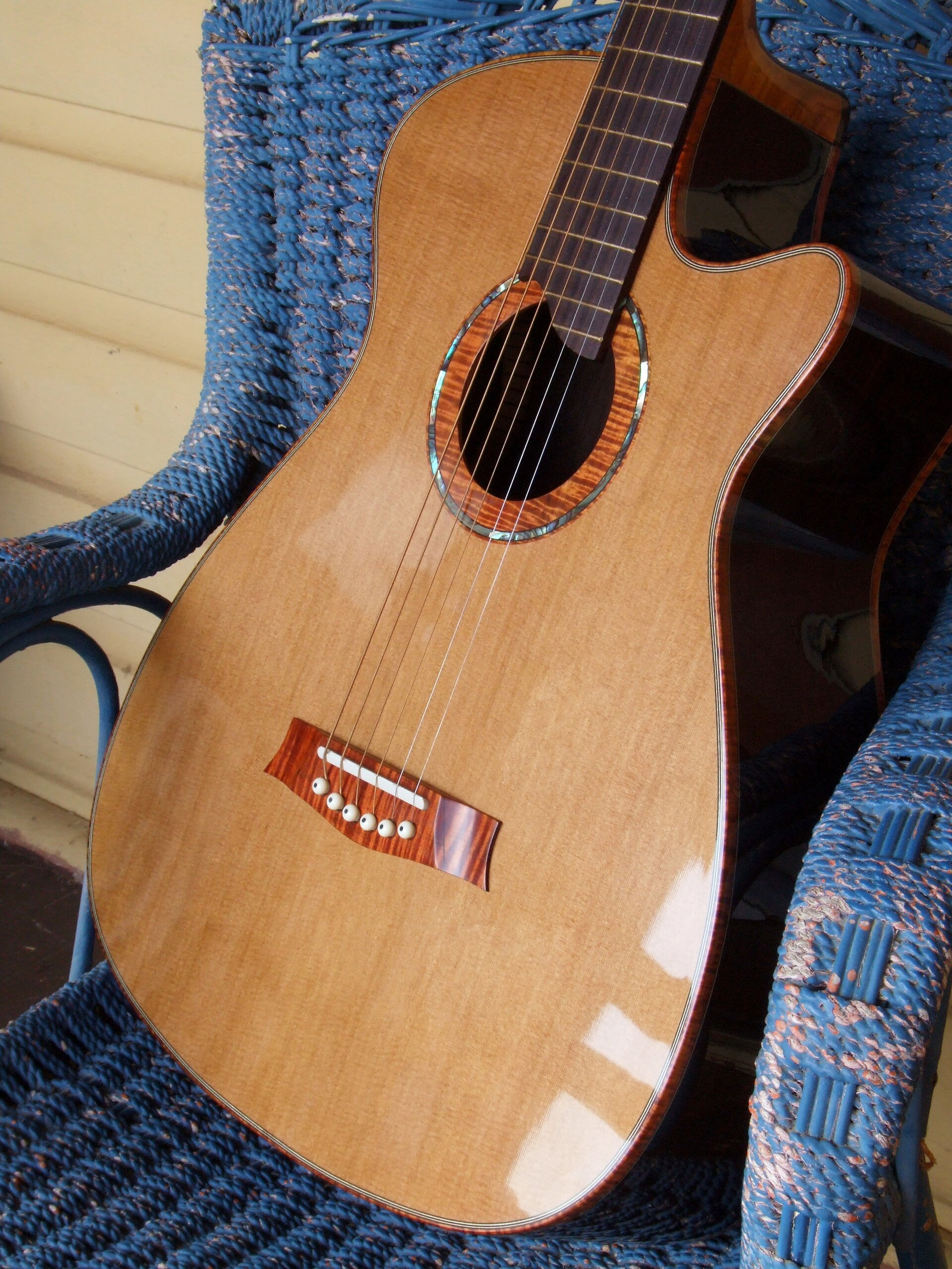 Cedar and rosewood steel string guitar sat on a blue wicker chair