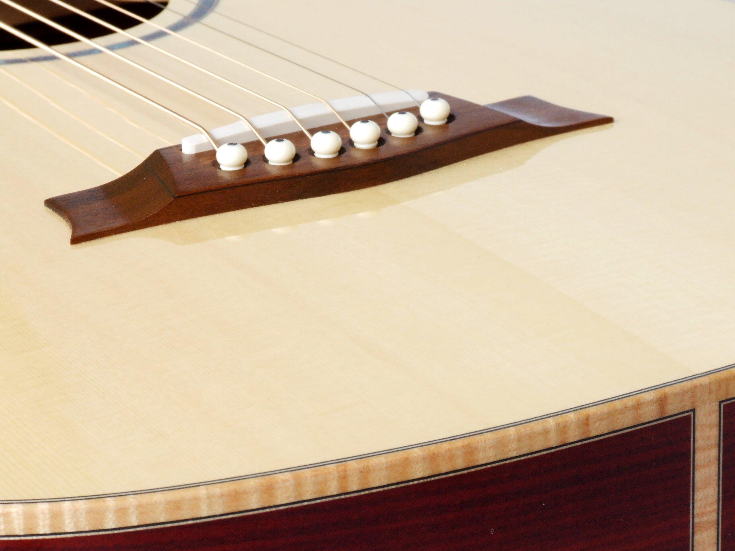 Carbon fibre reinforced bridge on a steel string guitar