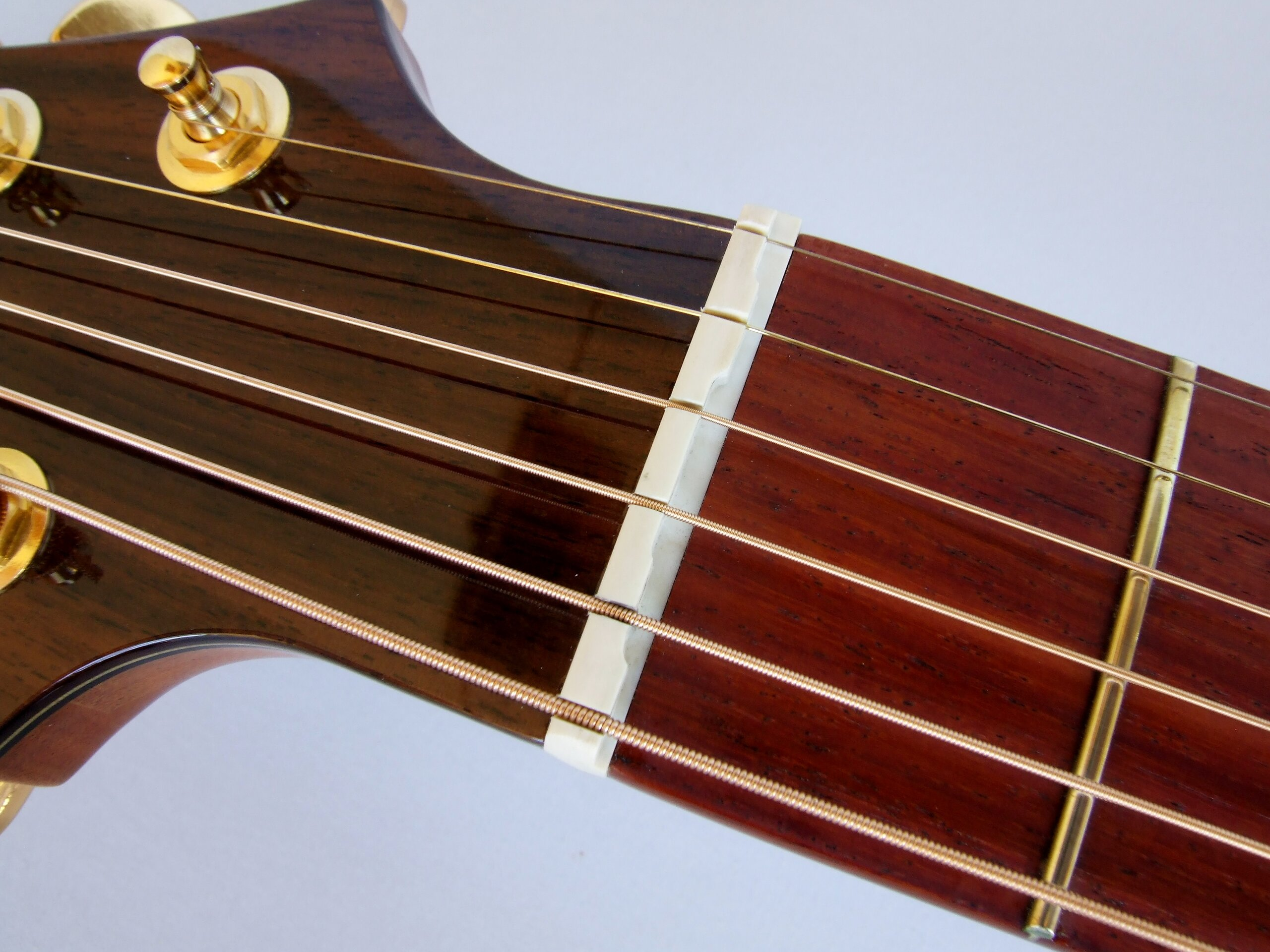 Detail of compensated nut on a steel string guitar