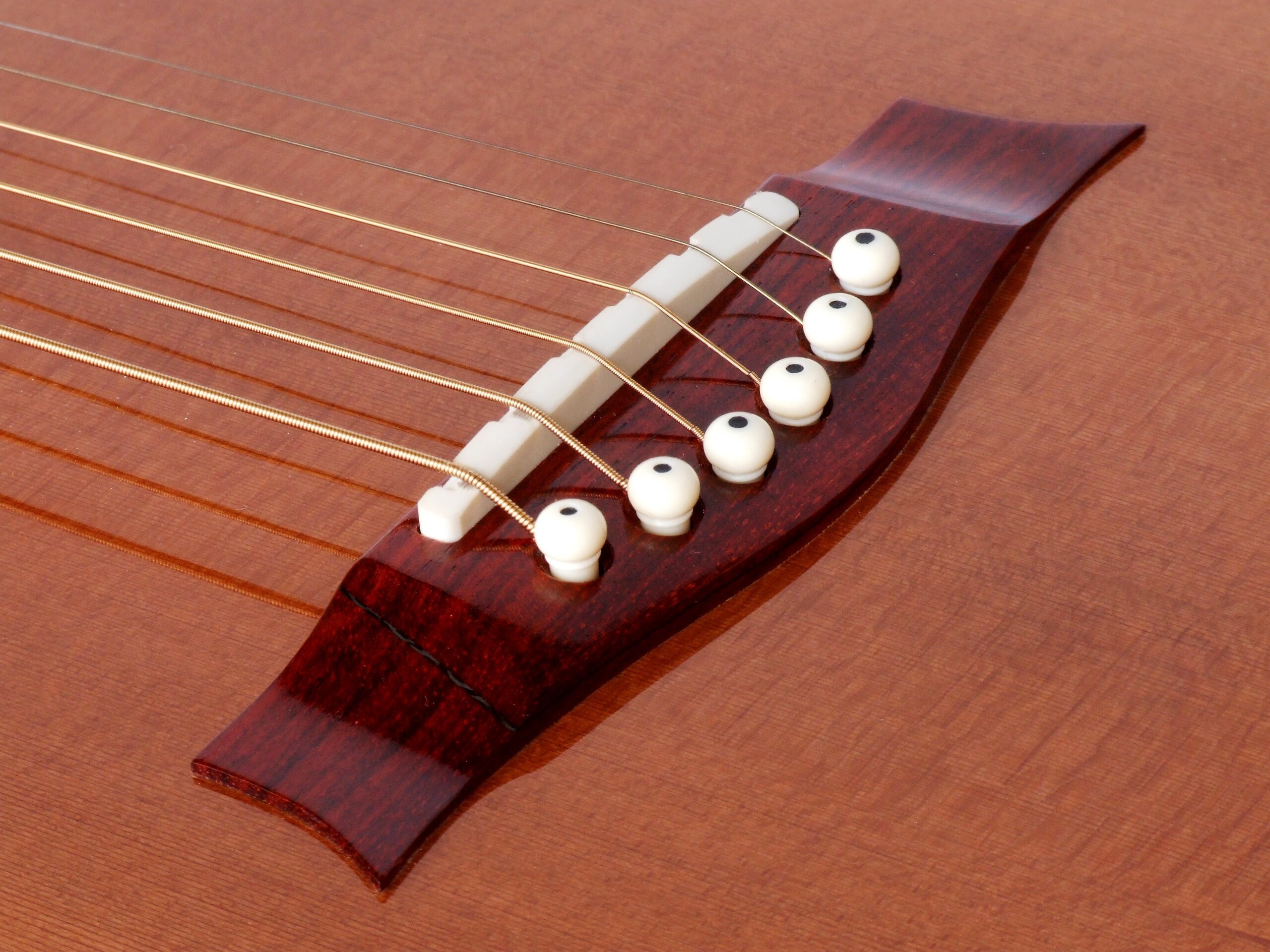 Carbon fibre reinforced bridge on a steel string guitar with a redwood top