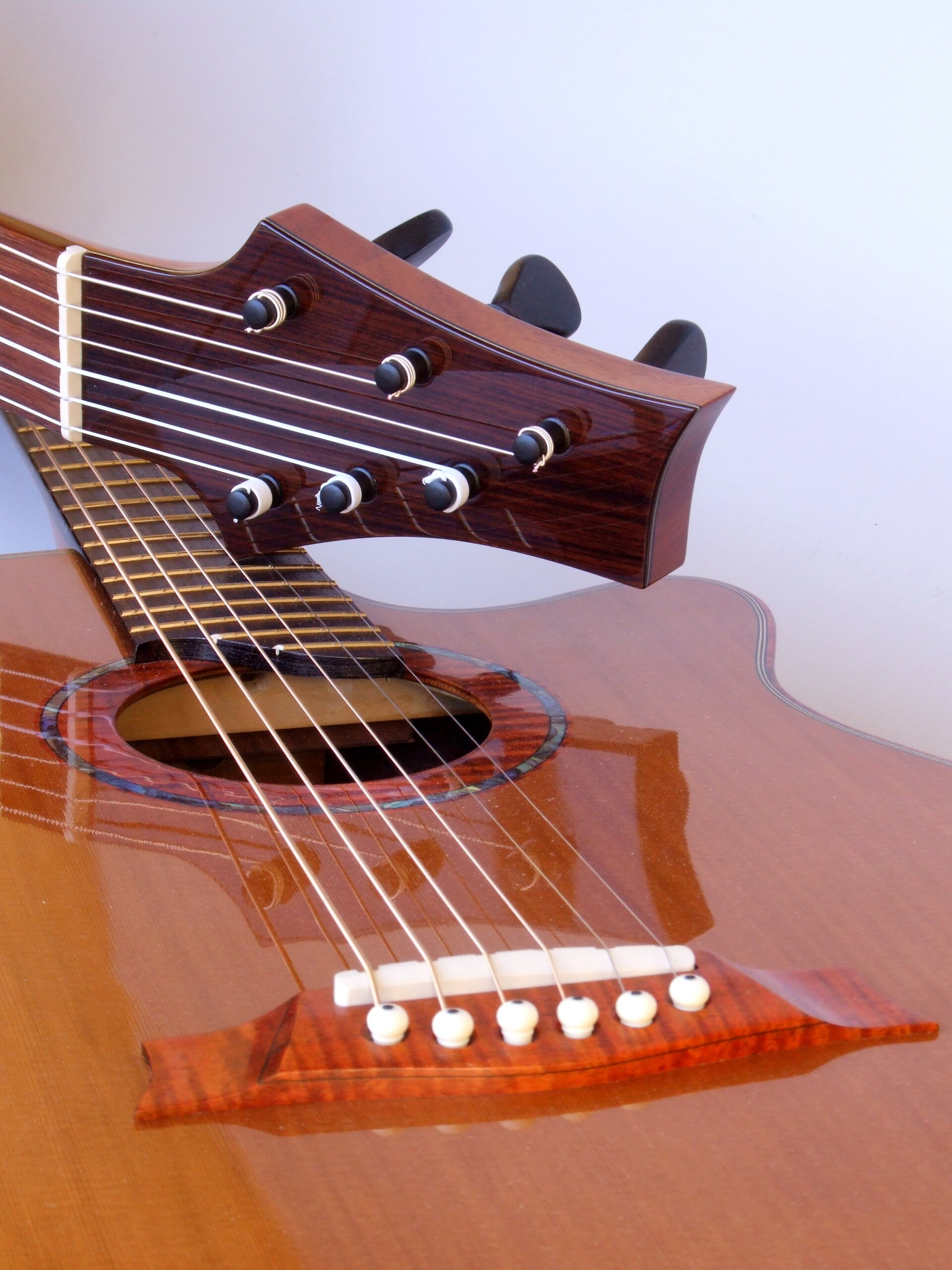 Classical guitar headstock resting on a steel string guitar