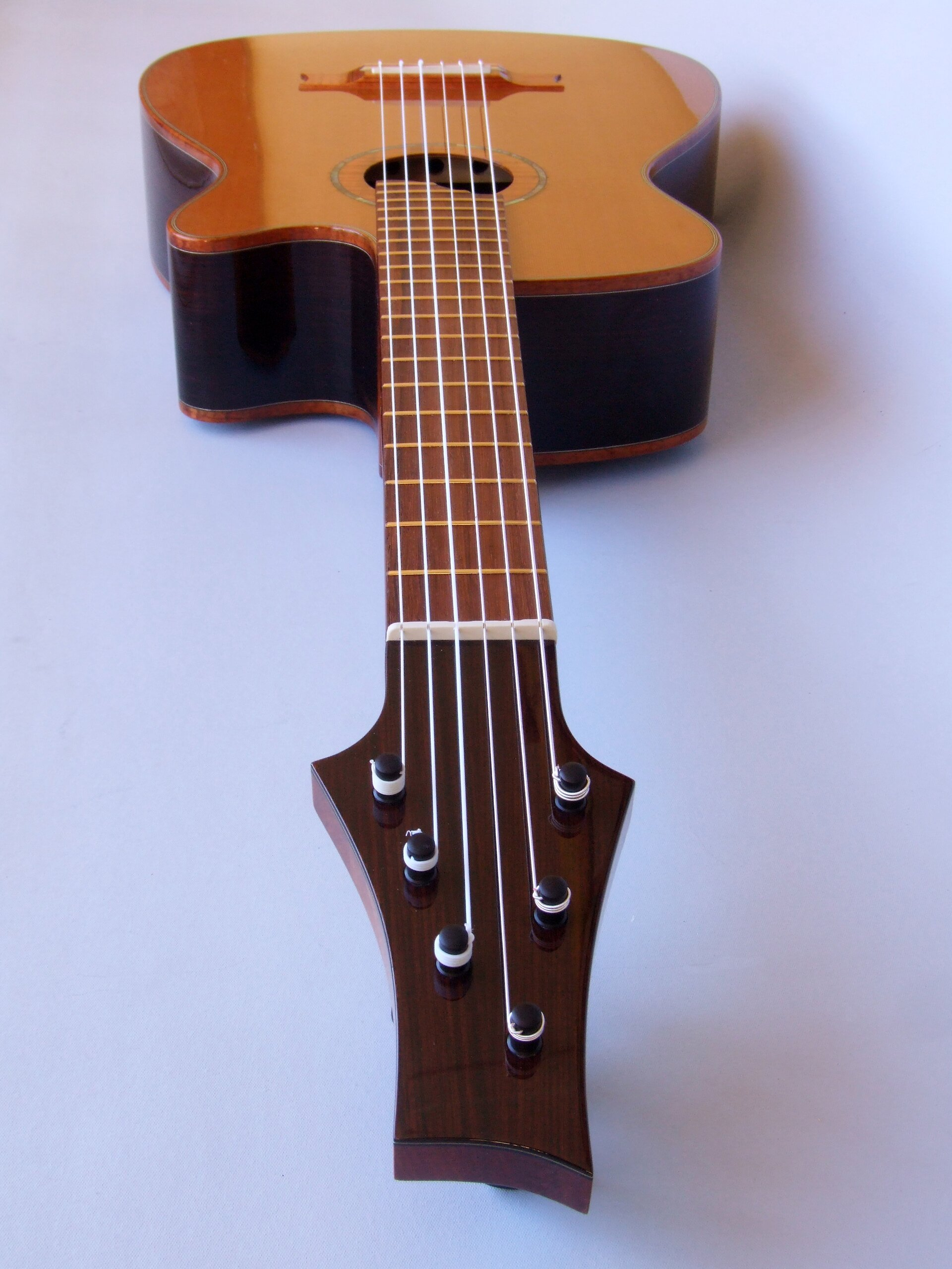 Looking down the neck of a cedar topped cutaway classical guitar with planetary peg tuners