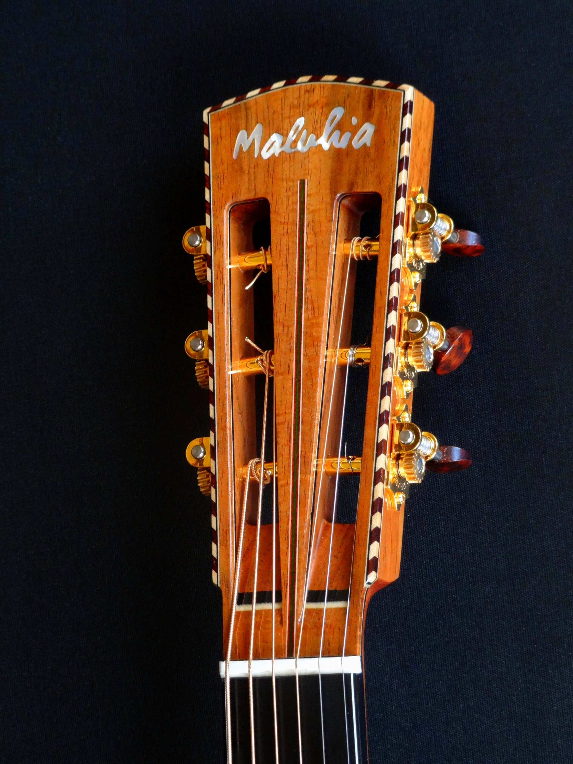 Slot headstock with rope binding, pearl inlay and Waverly tuners