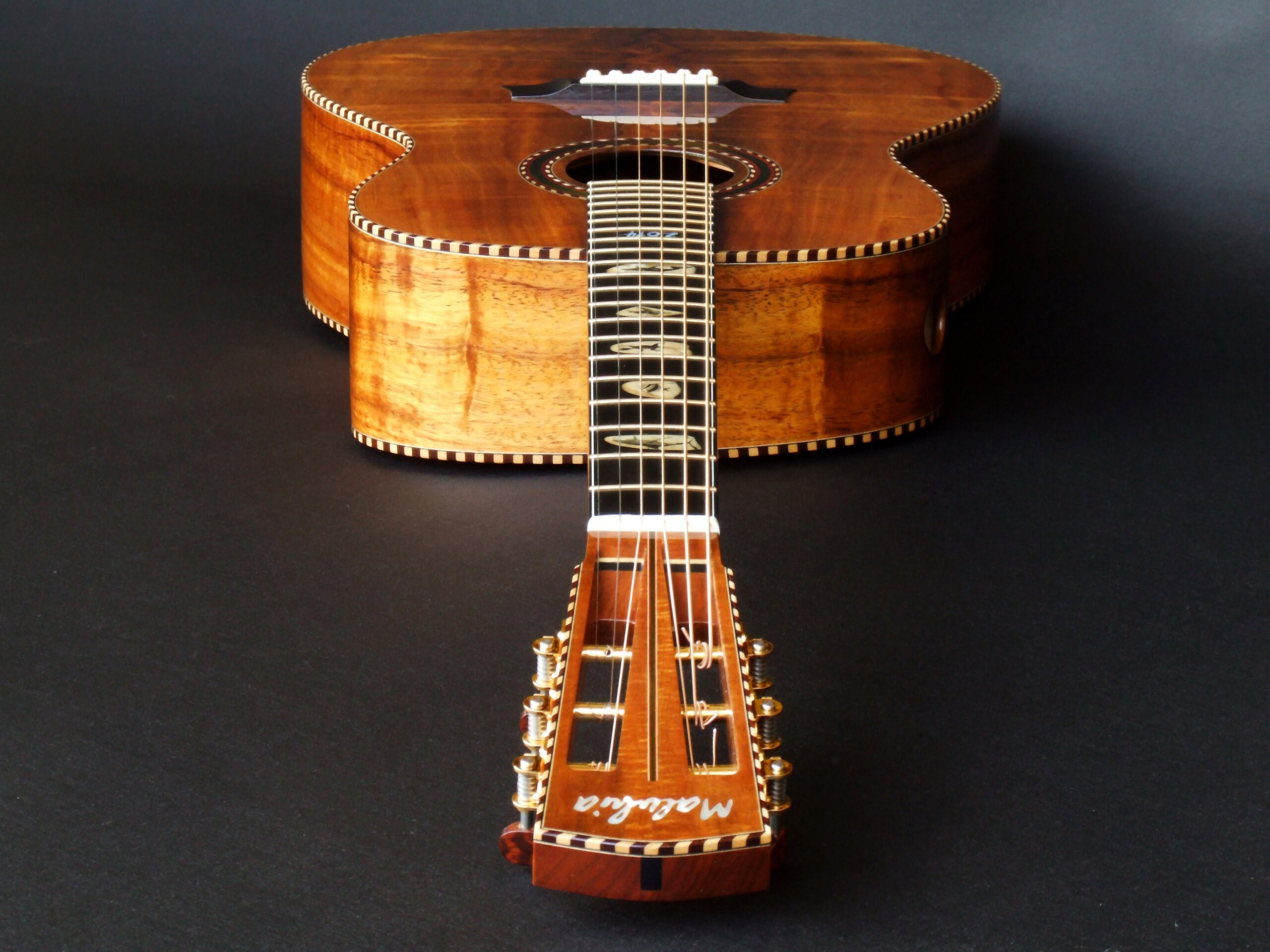 Looking down the neck of a figured koa wedge bodied guitar by Trevor Gore