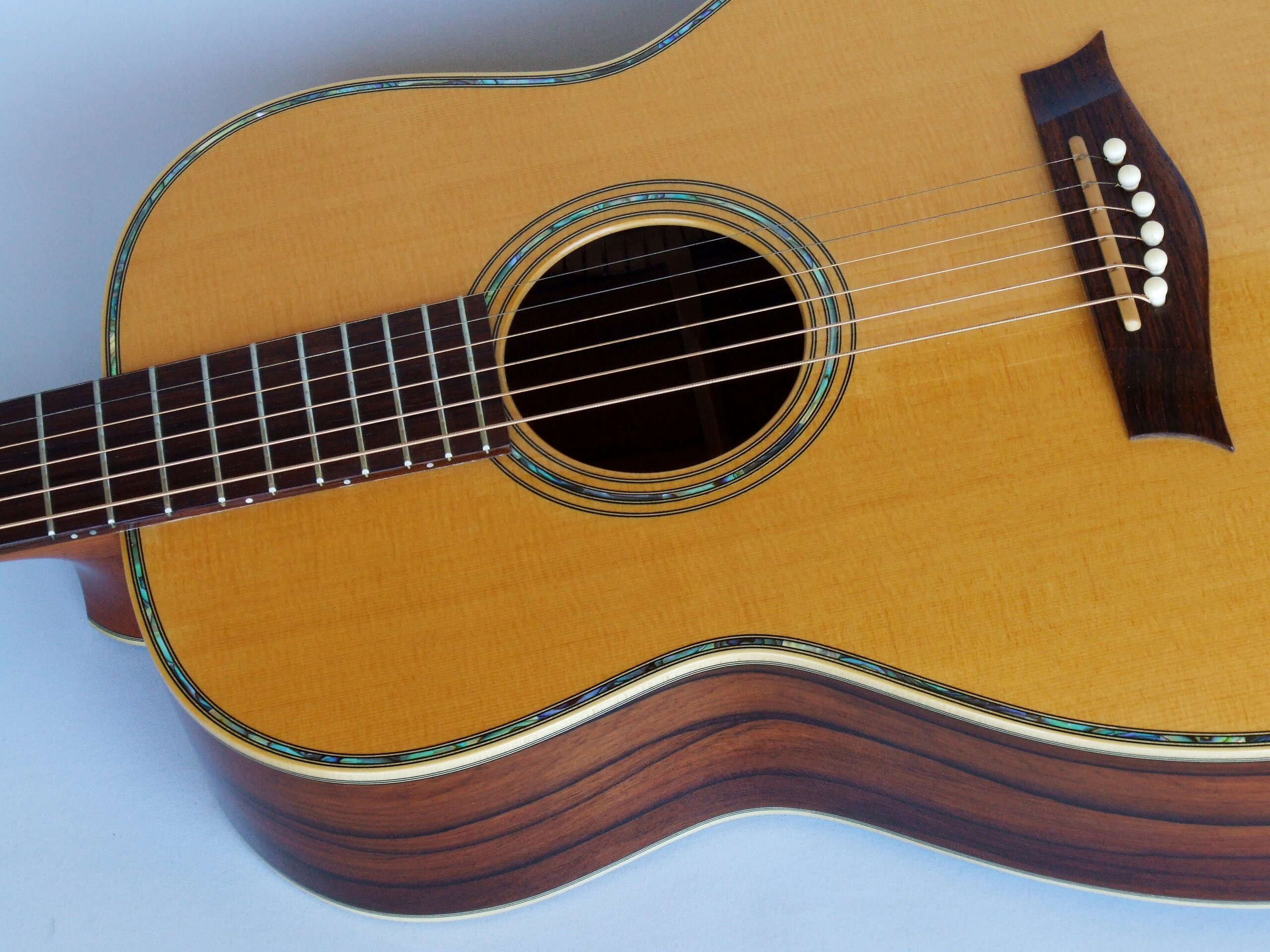 Aged spruce top on a 12 fret 00 guitar with paua decoration