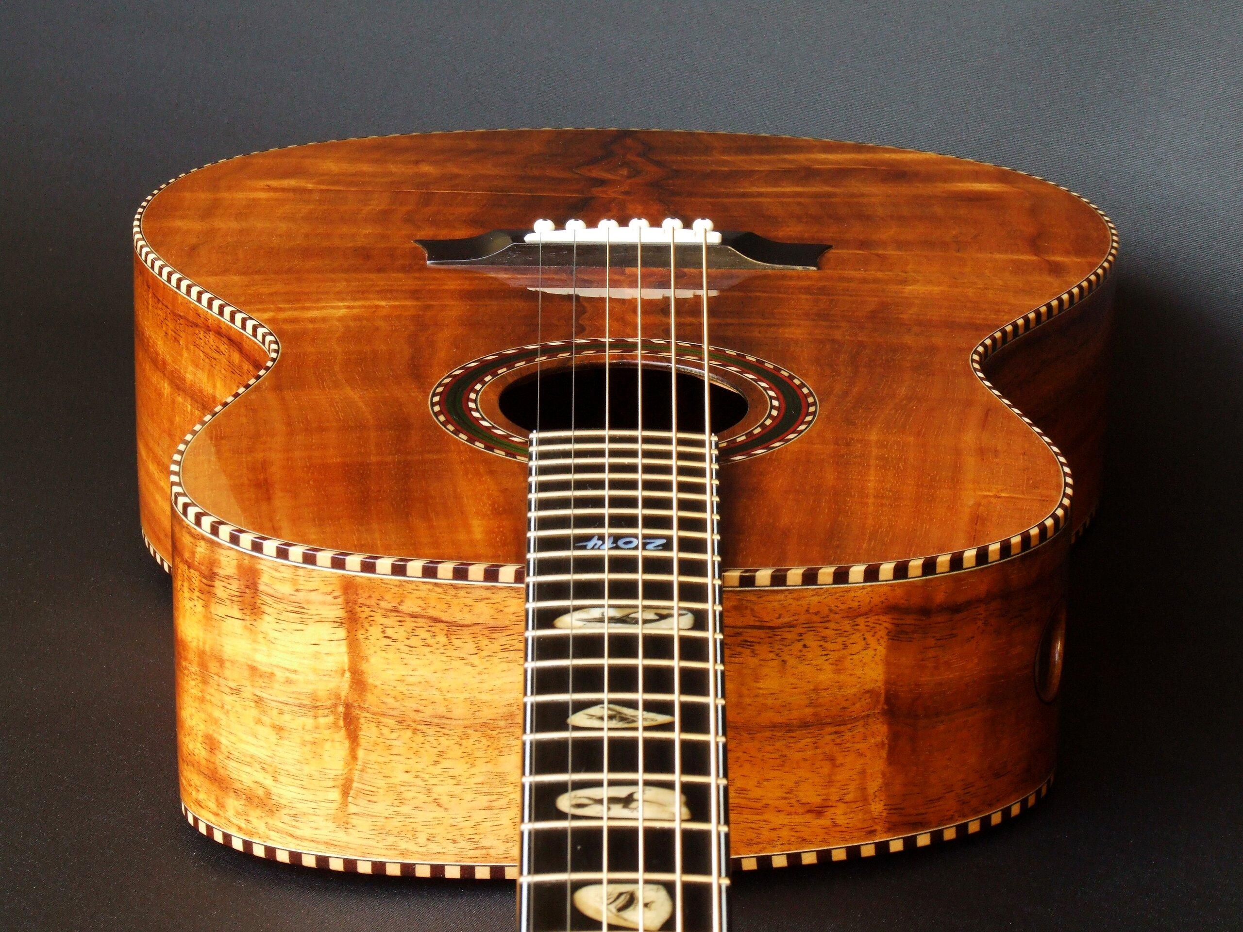 Wedge-shaped body on a figured koa guitar by Trevor Gore