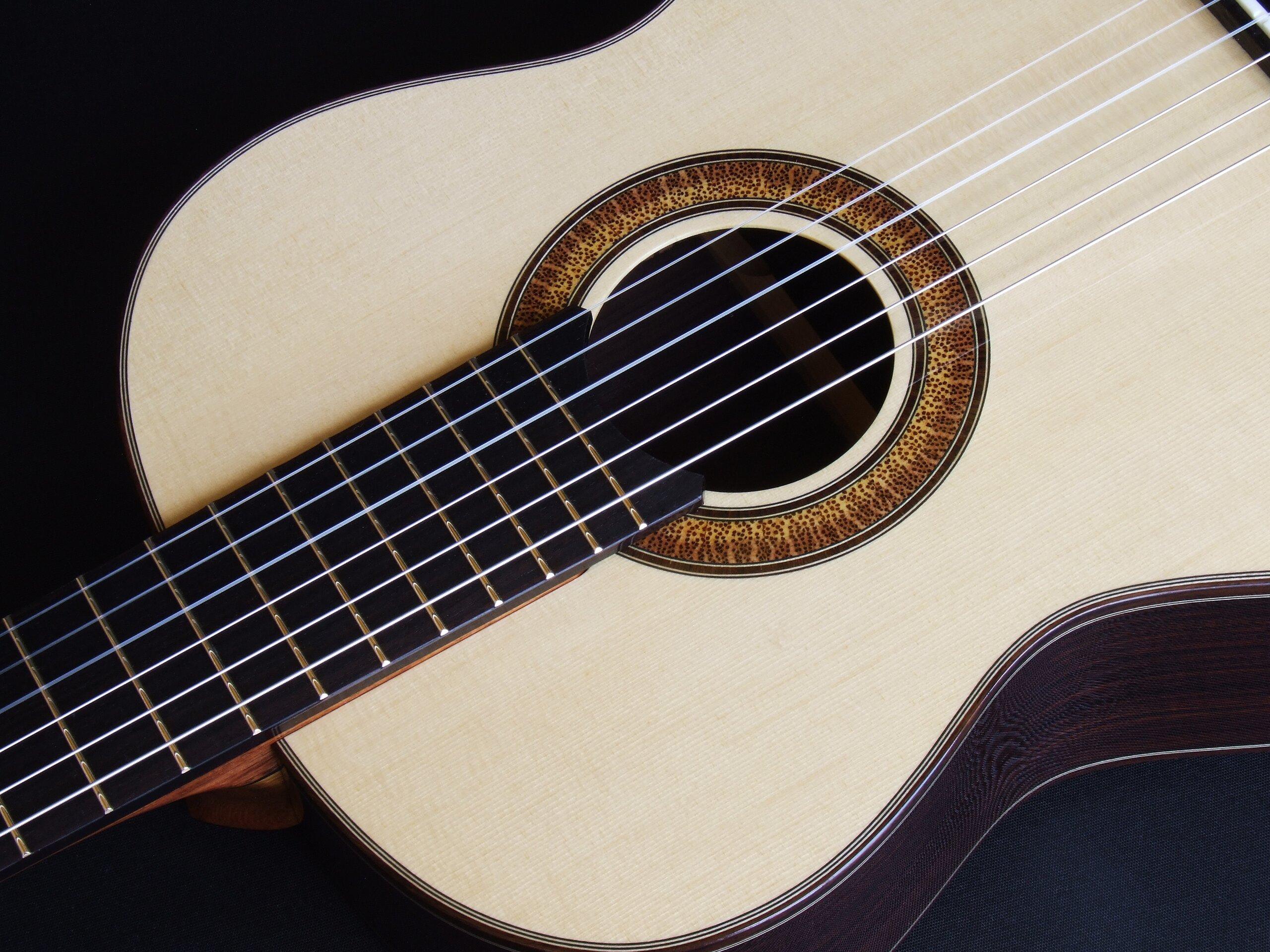 Natural sunburst rosette in a small body classical guitar top