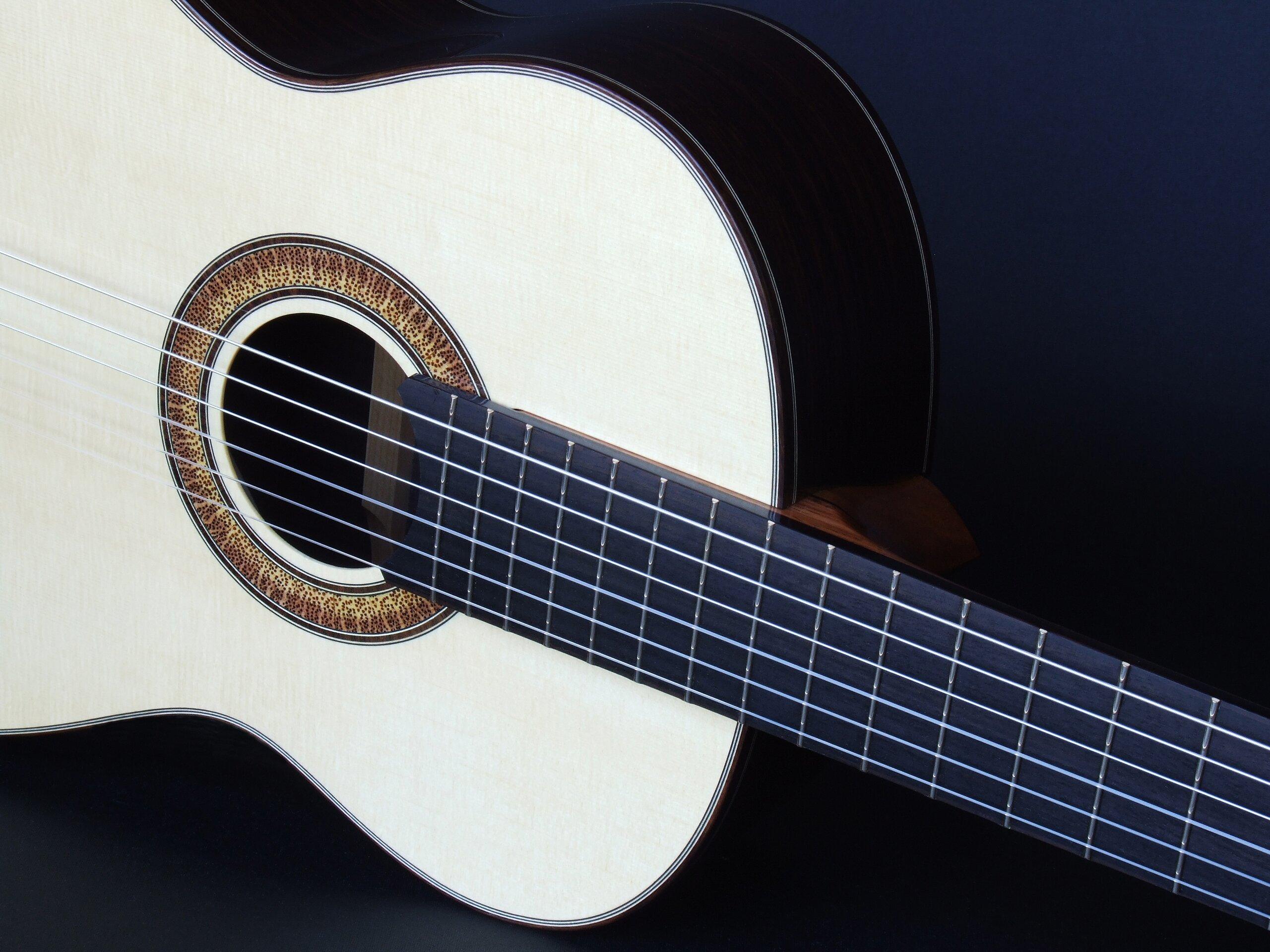 Natural sunburst rosette and ebony fretboard on a classical guitar