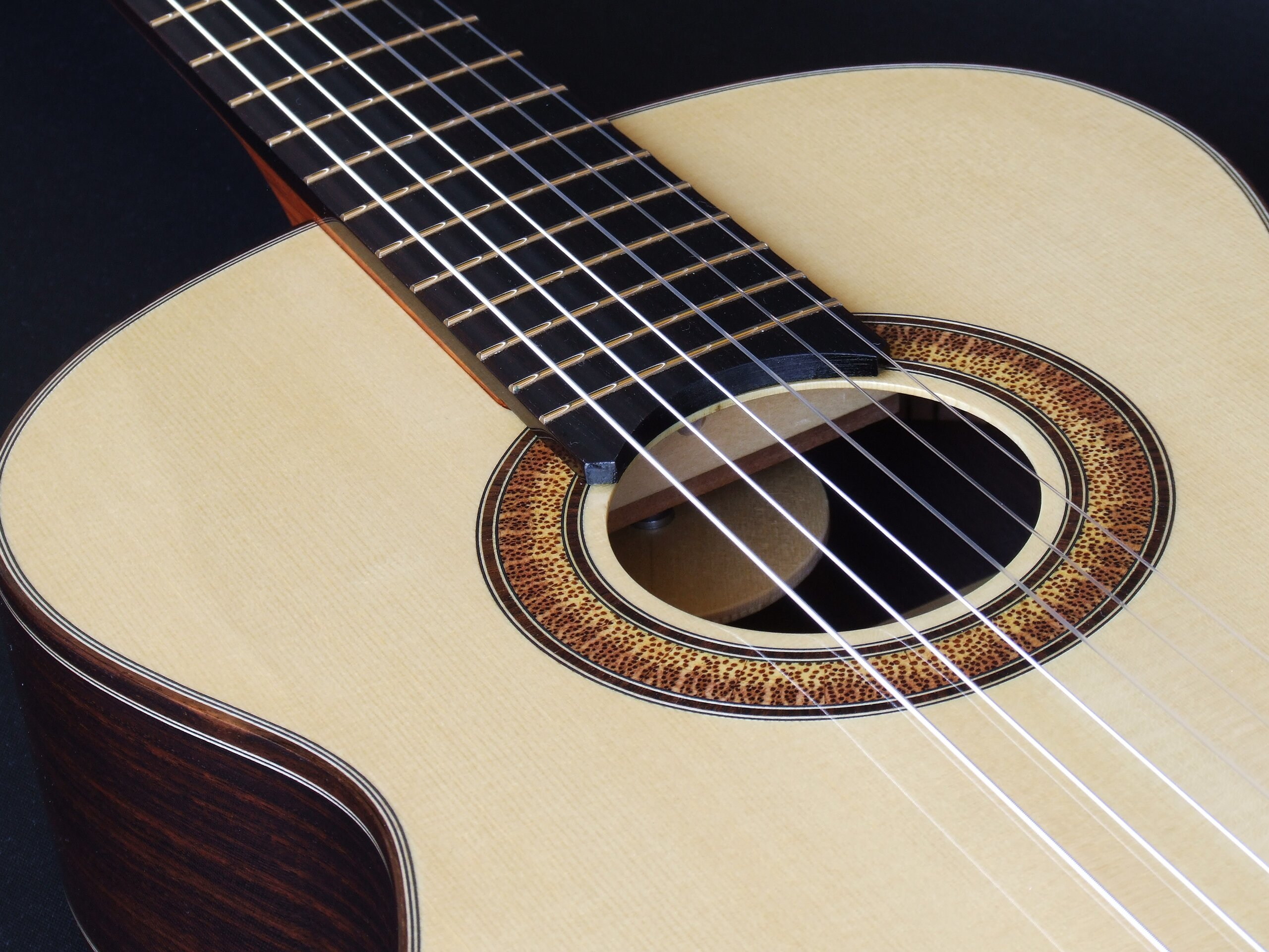 Classical guitar with a tilt neck showing the adjustment wheel through the sound hole