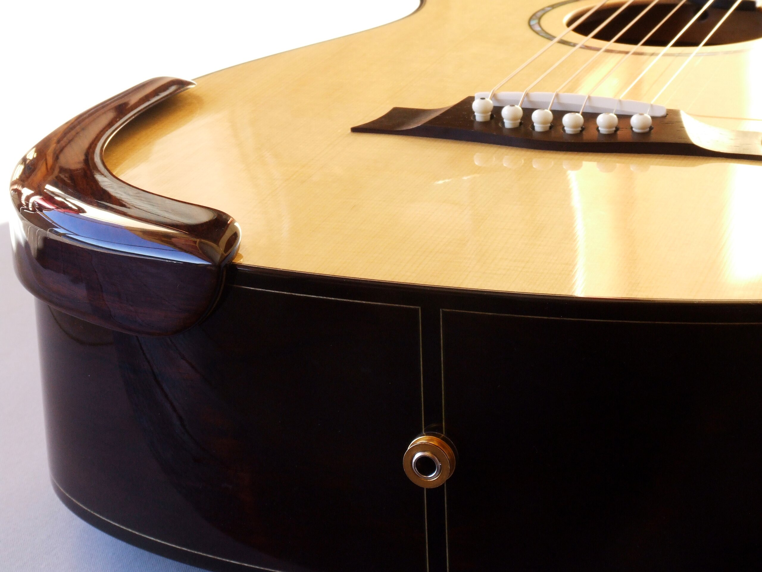 Arm rest on a small body steel string guitar in Lutz spruce and Brazilian rosewood