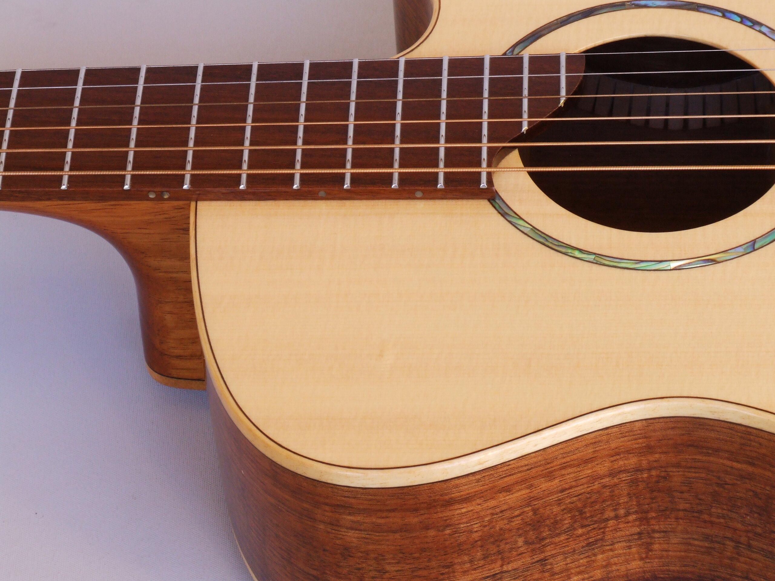 Fret board end on a small body steel string guitar