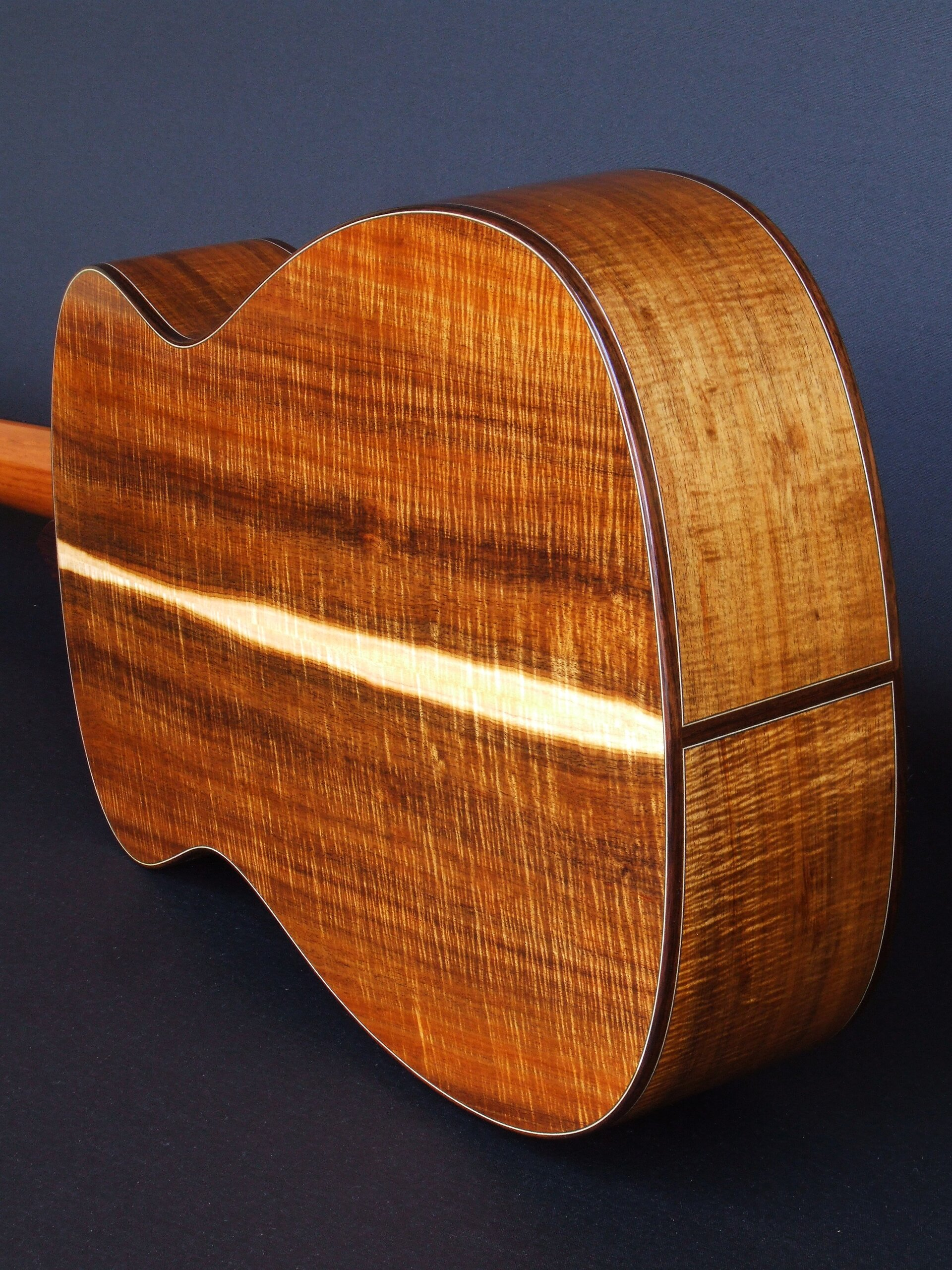 The back and sides of a guitar made with highly figured Australian Blackwood