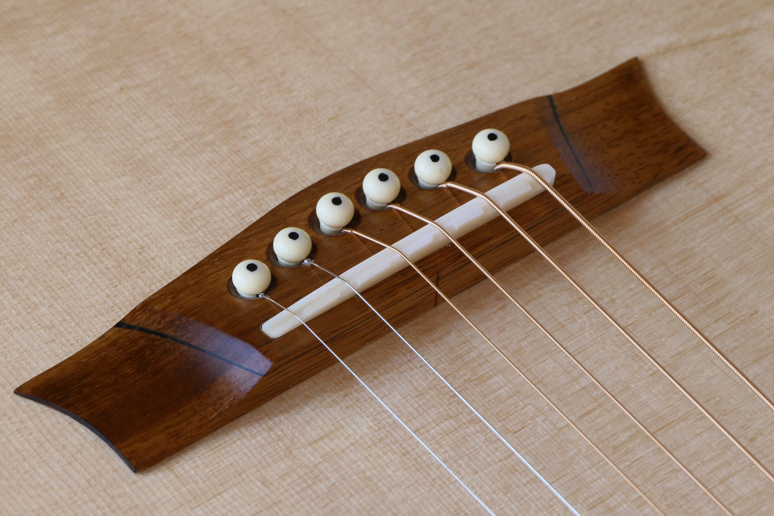 Steel string guitar bridge with Trevor Gore compensation on the saddle